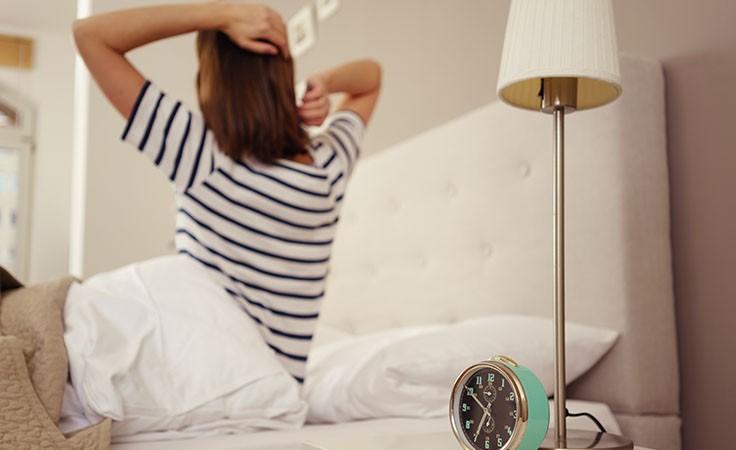 Schlafstörungen: Frau streckt sich im Bett