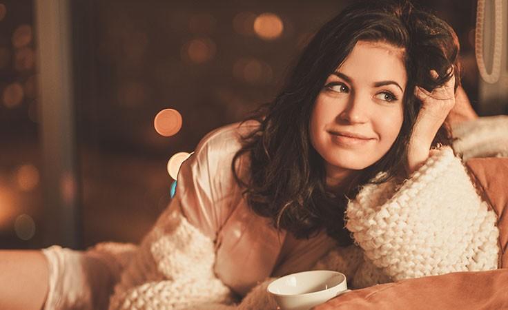 Frau trinkt Tee auf der Couch