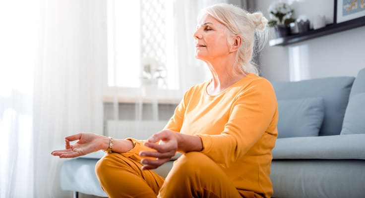 Aeltere Frau meditiert sitzend