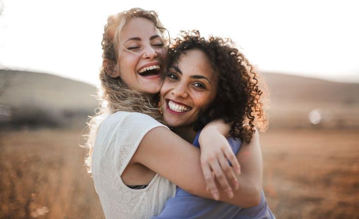 Zwei Freundinnen umarmen sich lachend