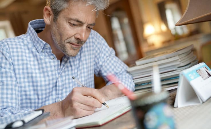 Mann am Schreibtisch notiert was im Journal